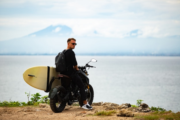 Young man sits on a motorcycle with a surfboard
