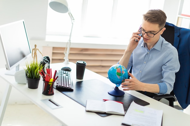 A young man sits in the office at a computer desk, talking on the phone and looking at the globe.