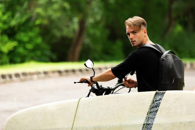 젊은 남자가 서핑 보드와 함께 오토바이에 앉아