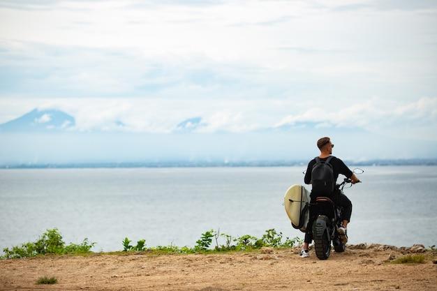 Молодой человек сидит на мотоцикле с доской для серфинга