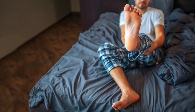 젊은 남자가 침대에 앉아 카메라에 그의 발을 보여줍니다. 그는 양손으로 다리를 잡습니다. 남자가 침실에 있어요. 보기를 자릅니다.