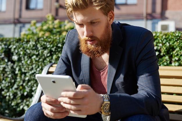 Молодой человек сидит на скамейке и использует интернет через планшет для чата или игры на открытом воздухе