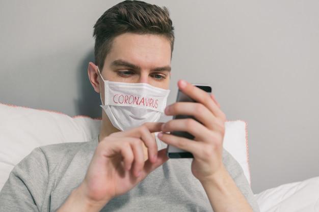 Молодой человек сидит на телефоне в постели