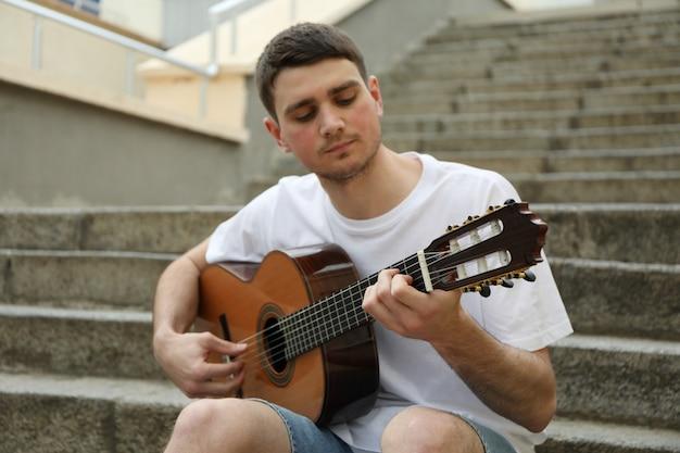 若い男が階段に座って、ギターで遊ぶ