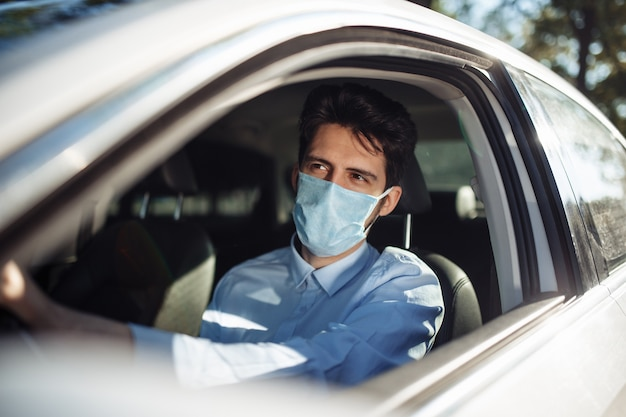 Young man sits behind the steering wheel in the car wearing sterile medical mask. social distance, virus spread prevention and treat concept.