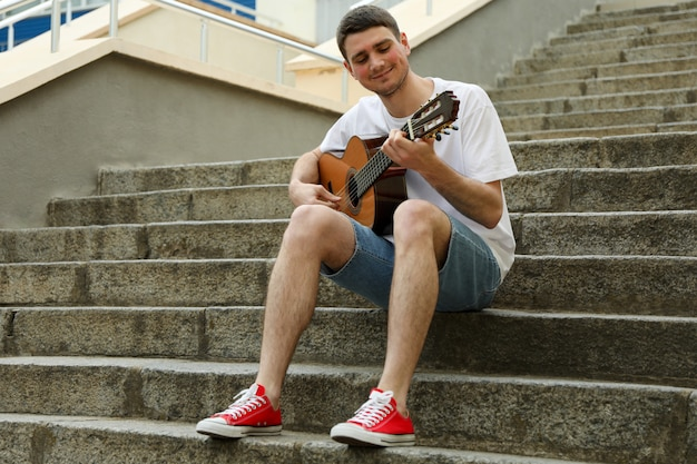 Young man sits on the steps and play on guitar