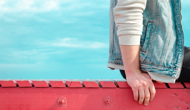 A young man sits turned sideways on a red wooden pier against a bright blue sky. summer lonely man travel banner with space for text