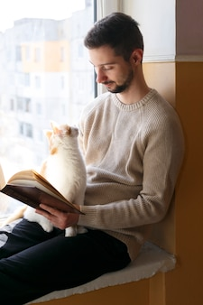 A young man sits on a windowsill and reads a book. next to the man sits a white cat with red spots. a man is wearing a beige sweater.