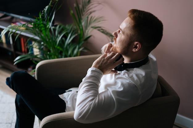 若い男は、ヘッドホンを耳から外して座って、思慮深く楽しみにしています。ホームリラクゼーションの概念。