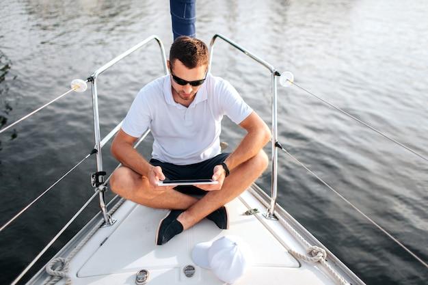 젊은 남자가 그의 다리를 건너 앉아 손에 태블릿을 잡아. 그는 침착하고 집중적입니다. 화면이 검은 색입니다. 남자는 요트 활에 앉아있다. 그는 선글라스를 쓴다.