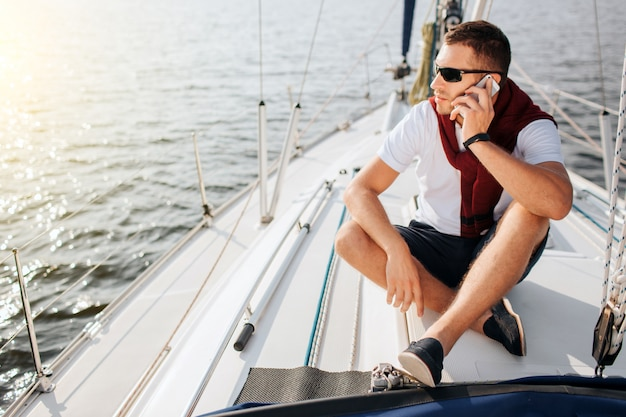 Young man sits on yacht board and look to left. he talks on phone. guy sits with legs crossed. he wears sunglasses. young man is busy.