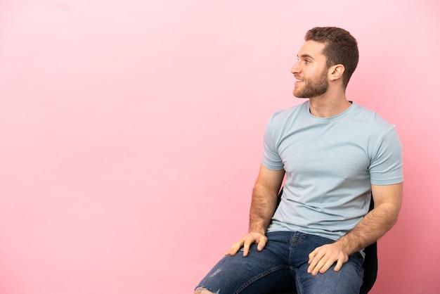 Молодой человек, сидящий на стуле, изолировал глядя сторону