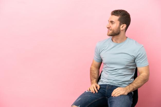 Молодой человек сидит на стуле изолированно смотрит в сторону и улыбается