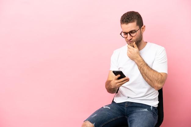 Молодой человек сидит на стуле изолированно, думая и отправляя сообщение