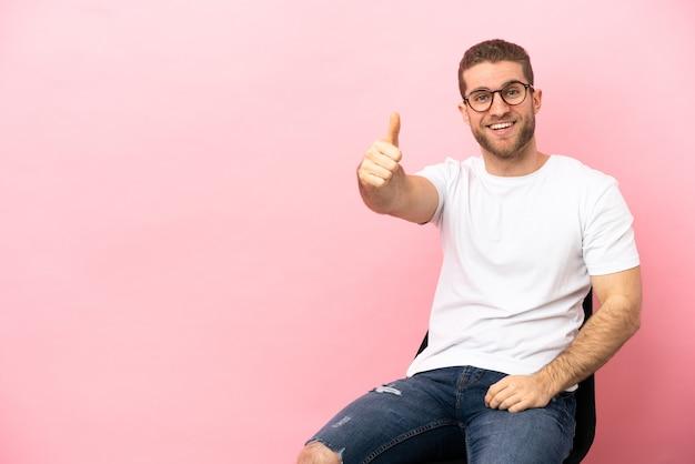 Молодой человек сидит на стуле изолированно с большими пальцами руки вверх, потому что произошло что-то хорошее Premium Фотографии
