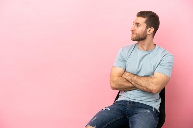 Молодой человек сидит на стуле над изолированным, скрестив руки