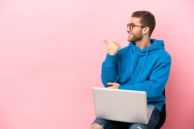 Молодой человек сидит на стуле с ноутбуком, указывая в сторону, чтобы представить продукт Premium Фотографии