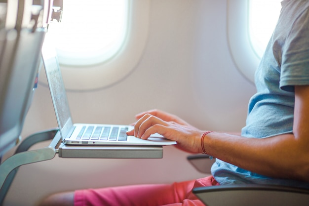 Young man sitting in the airplane and working on his laptop