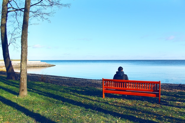 Young man sitting alone on a bench opposite the sea