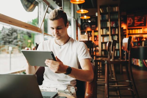 Молодой человек сидит и использует цифровой планшет за столом в уютном кафе