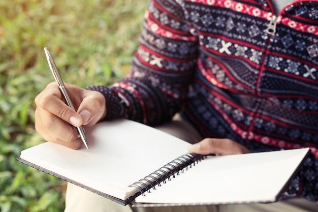 젊은 남자가 앉아서 펜을 사용하여 노트북에 쓰기