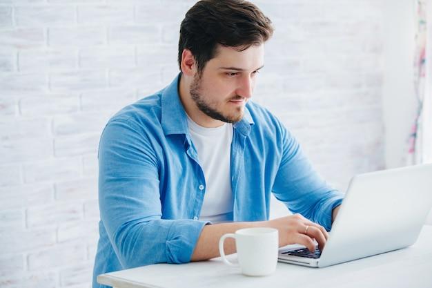 お茶を飲みながらスタジオのラップトップに座っている若い男