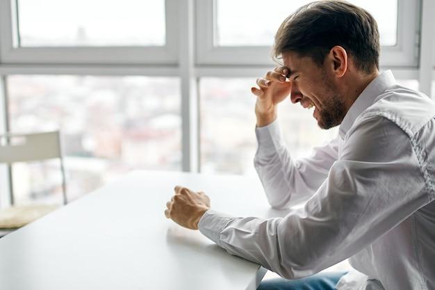 창 공간에 대해 우울 테이블에 앉아 젊은 남자