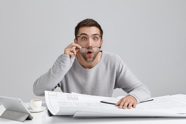 Молодой человек сидит за столом и делает документы