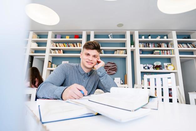 Молодой человек сидел на столе с книгами в библиотеке