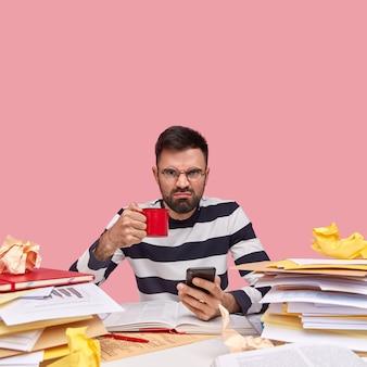 Молодой человек сидит за столом с документами и держит телефон