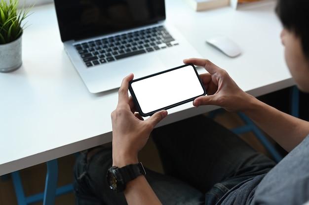 彼のワークスペースに座って、ソーシャルネットワークをチェックする水平携帯電話を保持している若い男
