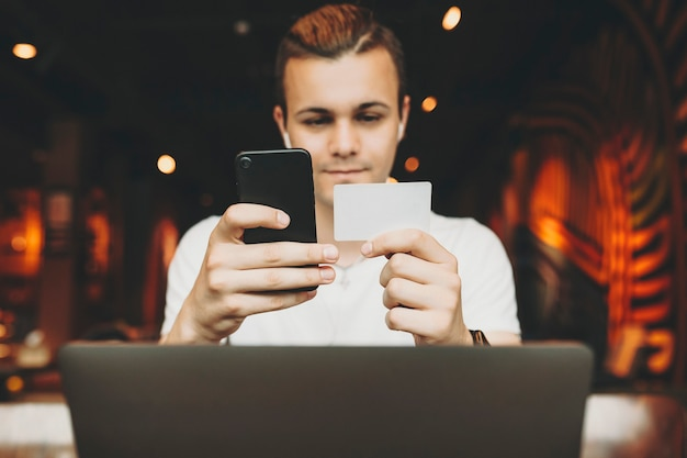 Молодой человек сидит за ноутбуком в кафе и держит пустую визитку и смартфон