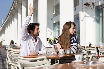 ウェイターを求める腕を上げた屋外カフェに座っている若い男