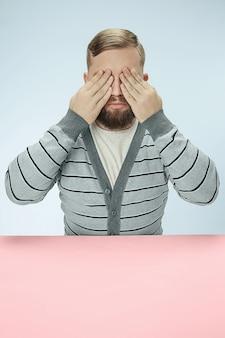 Молодой человек сидит за столом в студии с закрытыми глазами, изолированными на синем.