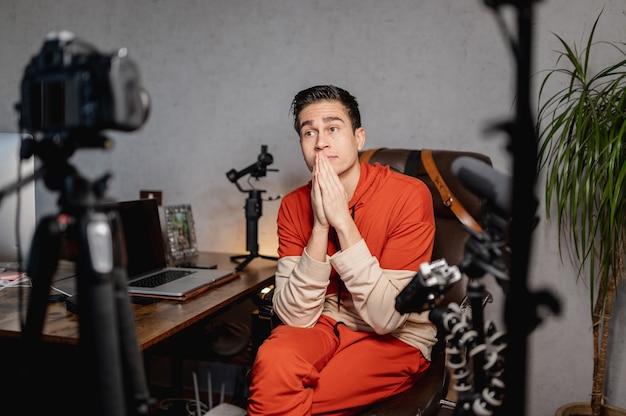 Молодой человек сидит за столом, разговаривает в камеру. парень записывает видео на профессиональном оборудовании. влог, концепция фрилансера.