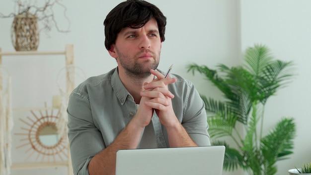 Молодой человек сидит за столом перед компьютером и думает о идеях решения проблемы поиска вдохновения