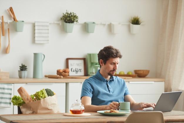 Молодой человек сидит за столом на кухне, пьет кофе и работает в сети, используя свой ноутбук