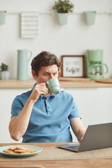 Молодой человек сидит за столом, глядя на монитор ноутбука и пьет кофе на домашней кухне