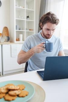 Молодой человек сидит за столом, работает на портативном компьютере и пьет кофе утром на кухне
