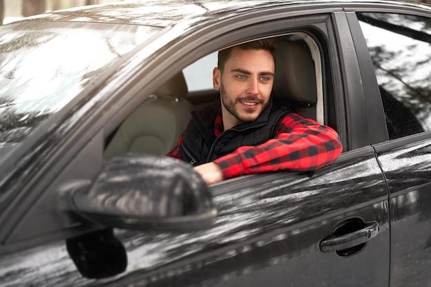 彼の車のホイールに座っている若い男