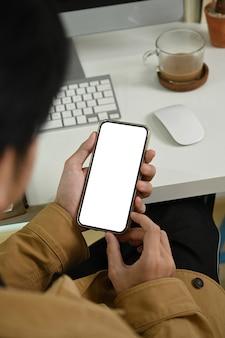Молодой человек сидит на рабочем месте и с помощью смартфона.