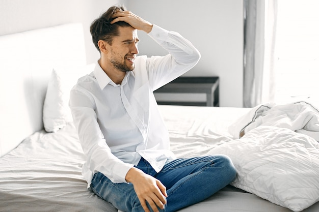 Young man sitting on bed depressed