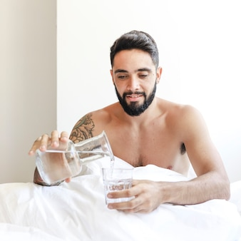 Young man sitting on bed pouring water in glass