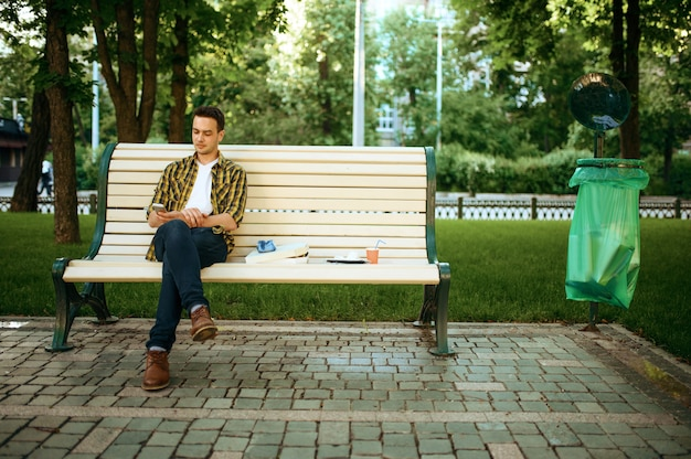 Young man sitting on bench among the trash in park, volunteering. ecological restoration, eco lifestyle, ecology care, environment cleaning concept
