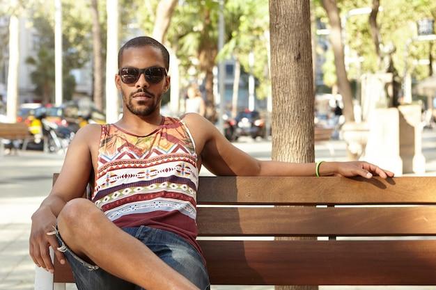 Giovane uomo seduto su una panchina nel parco