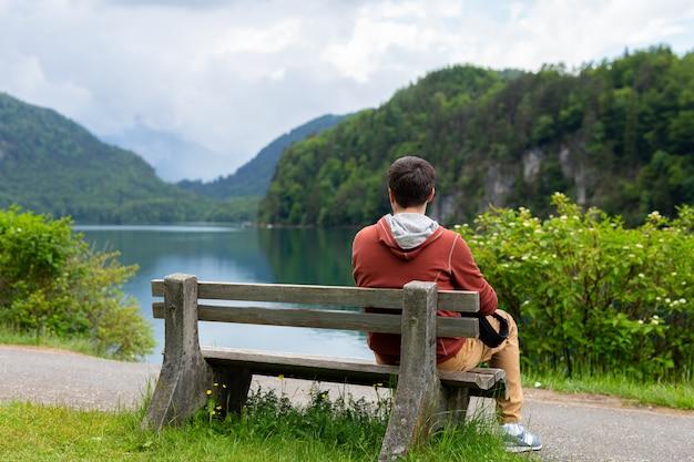 Young man sitting at bench