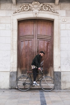 Young man sitting on the bicycle in front of vintage wooden door