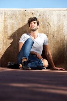 コンクリートの壁に座っている若い男が目を閉じた