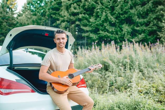 Young man sitting on a car playing guitar