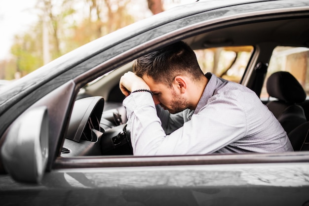 Young man sitting in car very upset and stressed after hard failure and moving in traffic jam
